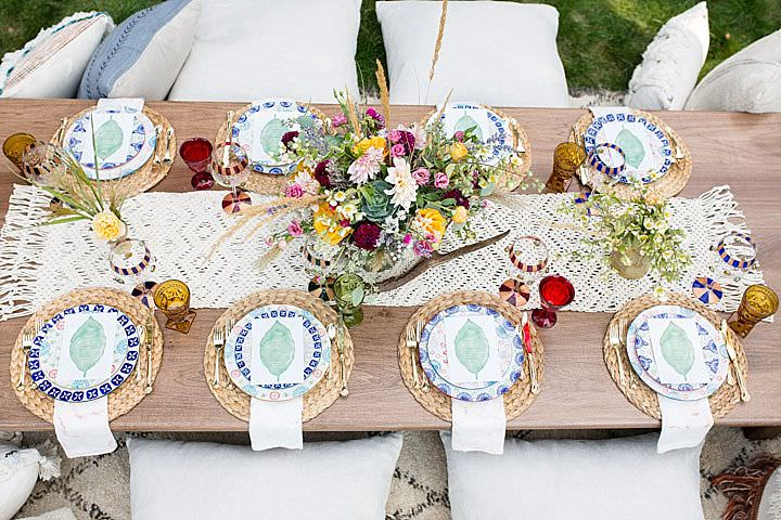 A macrame table runner, blooms, wicker chargers and colored glasses helped to created the look