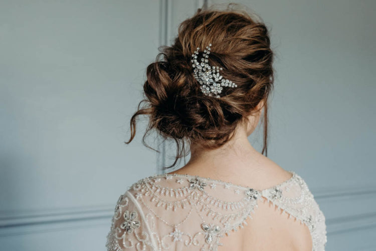 The bride was wearing a messy updo with a rhinestone hairpiece