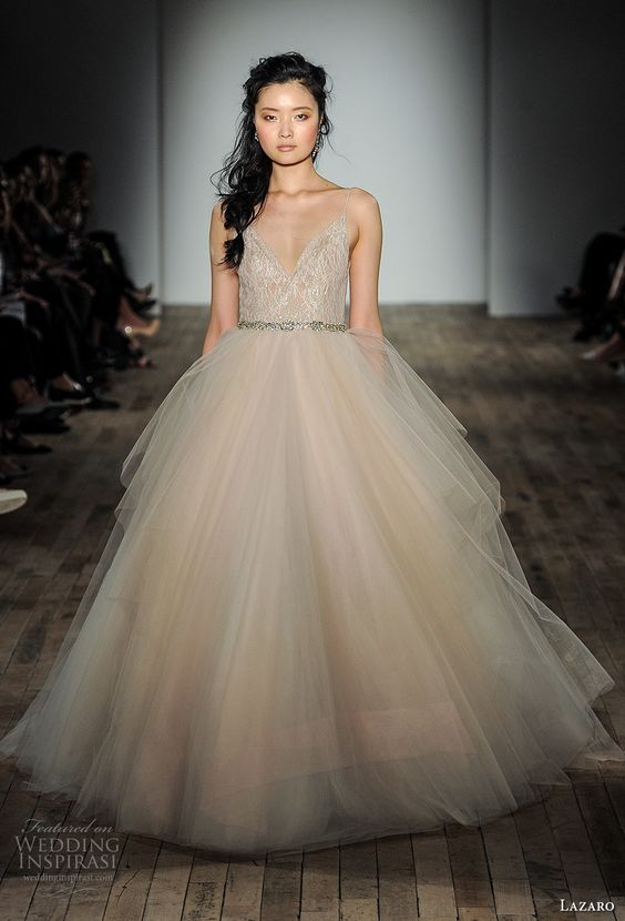 a champagne wedding dress with a lace bodice, spaghetti straps and a full layered skirt is accessorized with an embellished sash