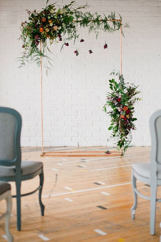 a copper pipe wedding arch with lush florals will do for many weddings