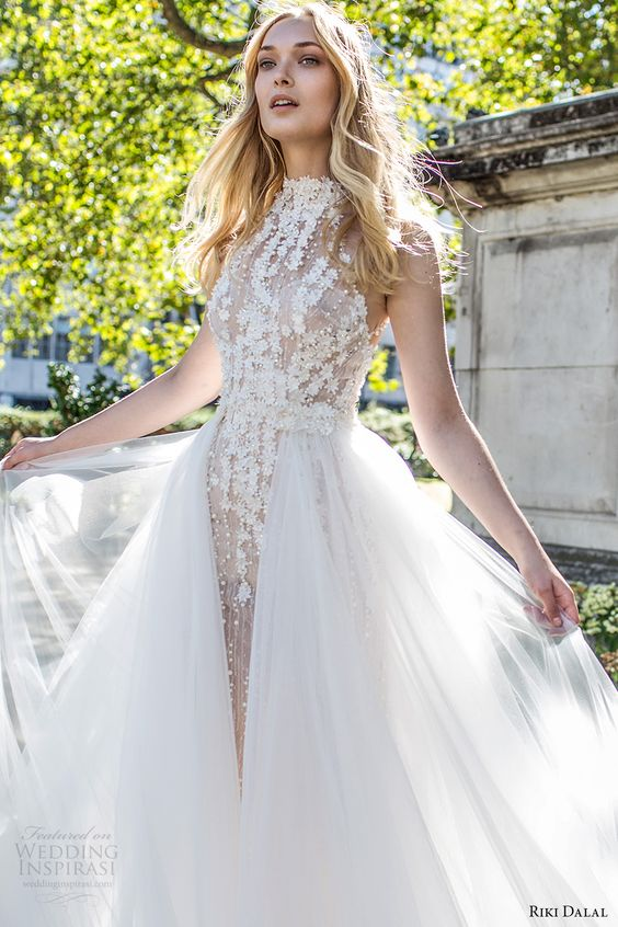 a high neckline floral lace applique sheath wedding dress and a layered tulle overskirt looks ethereal
