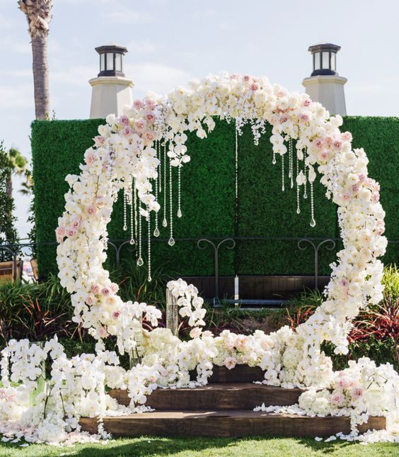 a luxurious circle floral arch with white and pink blooms and hanging crystals plus petals all around