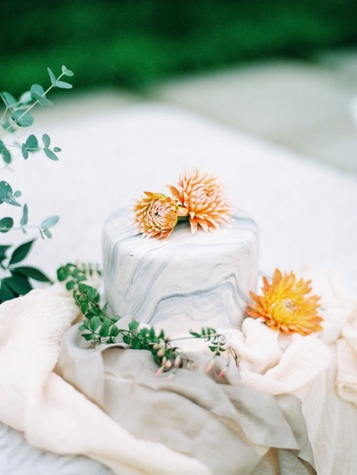 a one-layer grey marble wedding cake with orange blooms on top for a colorful touch