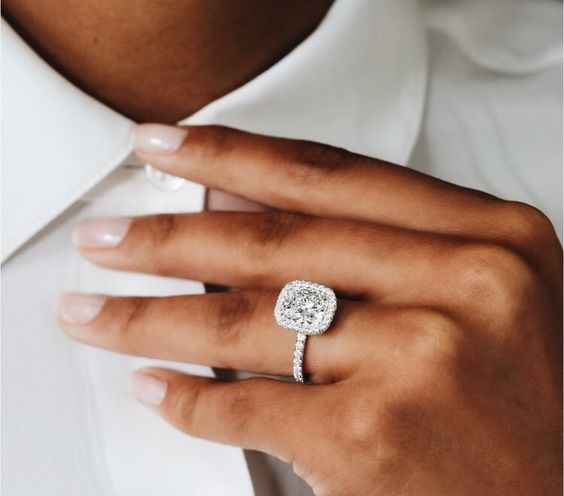 a super stylish white gold ring with a cushion diamond and a halo for an edgy look