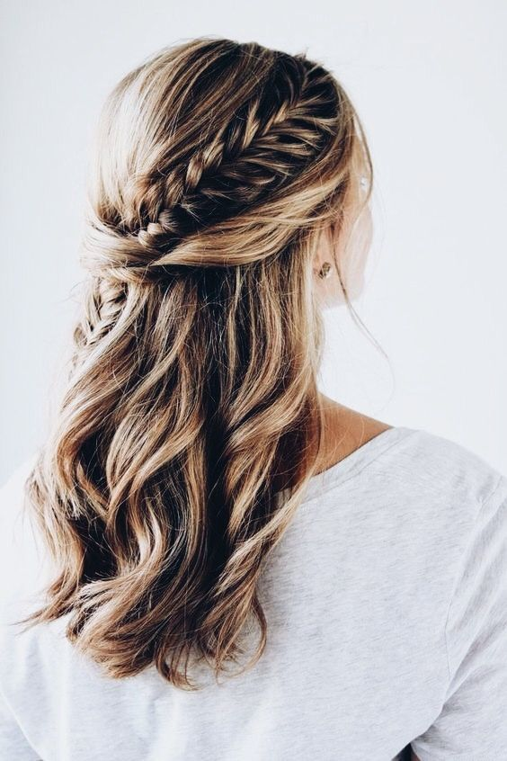 a twisted and braided half updo with messy beachy waves for a boho or free-spirited bride