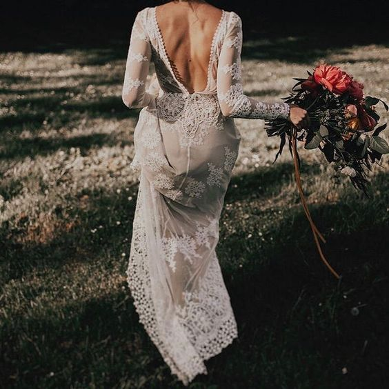 an amazing lace applique wedding gown with an A line silhouette, long sleeves and an open back