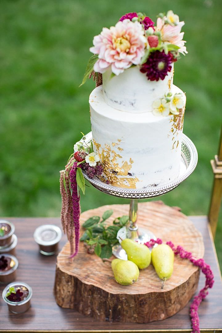 The wedding cake was decorated with gold leaf and lush blooms