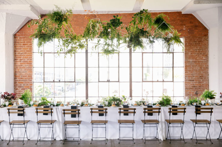 The wedding reception was an industrial one enlivened with fresh greenery and geometric decorations