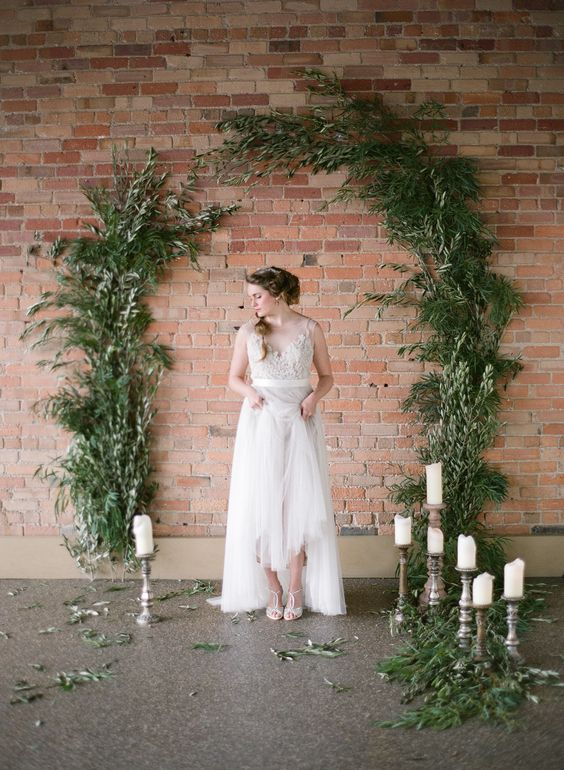 a greenery arch attached right to the brick wall and some candles around
