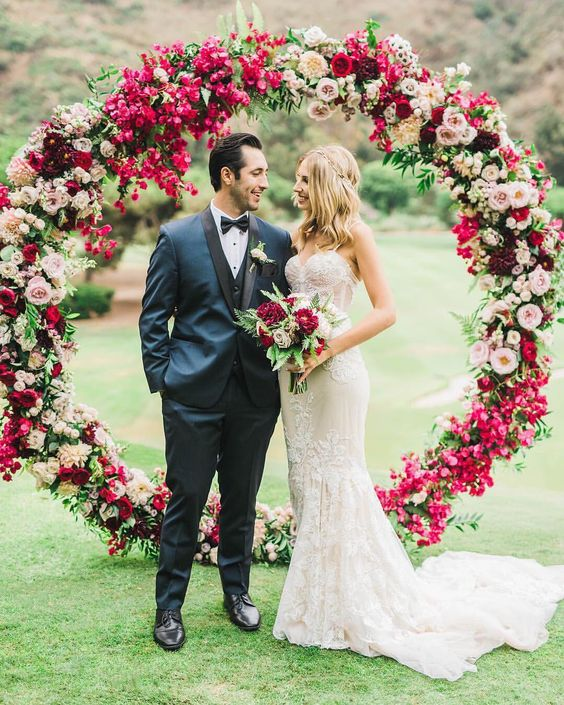 a lush circle wedding arch with fuchsia, red, pink and burgundy blooms for a colorful wedding