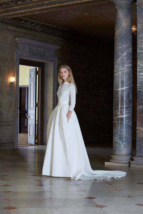 a white cable knit sweater with long sleeves over an A-line wedding gown