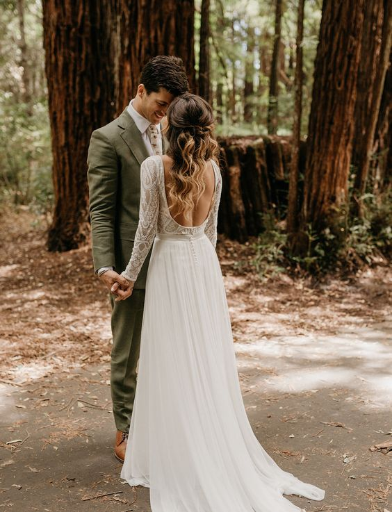 an A line wedding gown with a boho lace bodice, long sleeves, a cutout back and a flowy light skirt