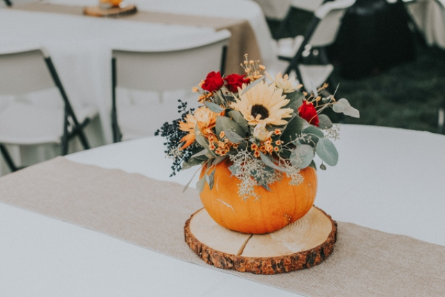 Some centerpieces were made of pumpkins, with greenery and bold blooms