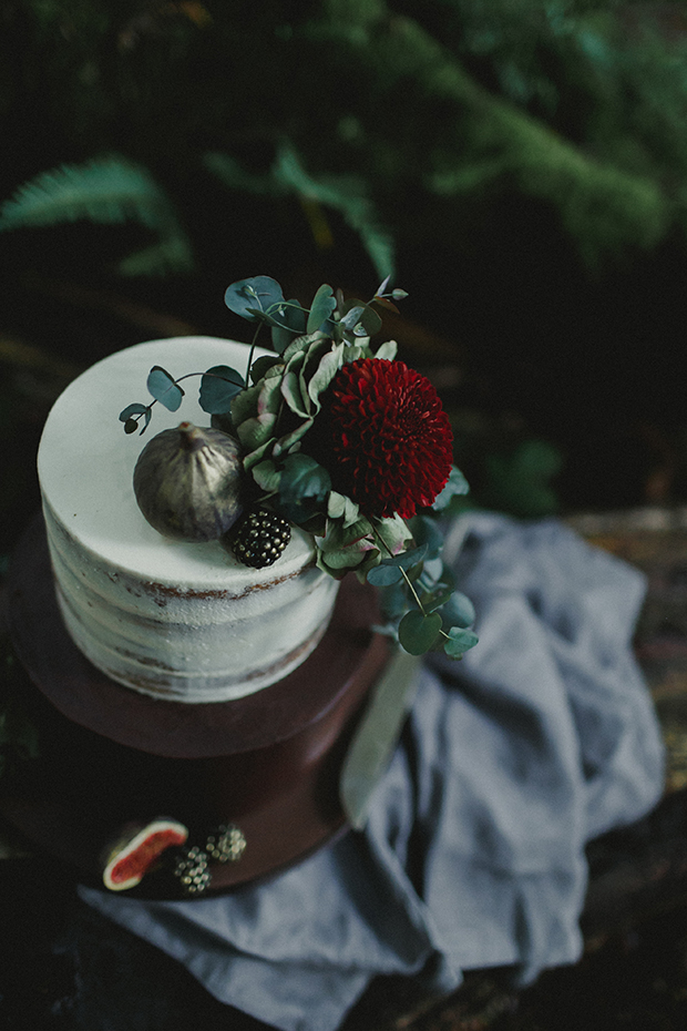 The moody wedding cake was a semi naked one with eucalyptus, a bloom and gilded fruit
