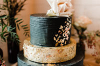 10 The wedding cake was a textural black and gold one with gold leaf decor and a blush bloom on top