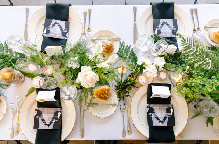 The wedidng tablescape was done in black, white and gold and with lots of greenery