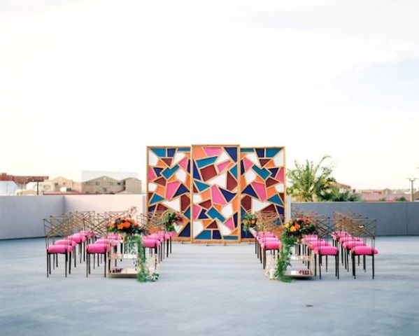 a colorful geometric backdrop with a mid-century modern feel and matching pink chairs