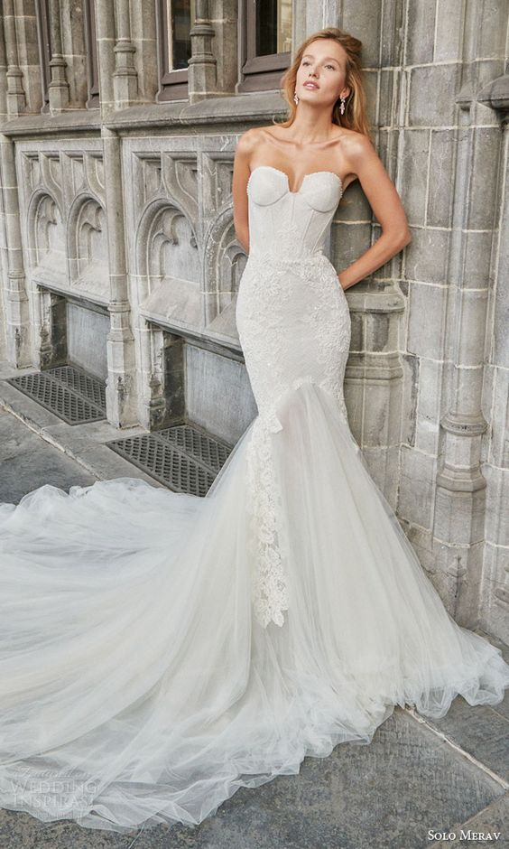 a creamy strapless corset wedding dress with lace appliques and a tulle tail with a train looks wow