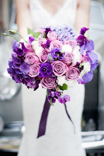 a lush wedding bouquet with violet, purple, pink and white blooms for a chic and bold look