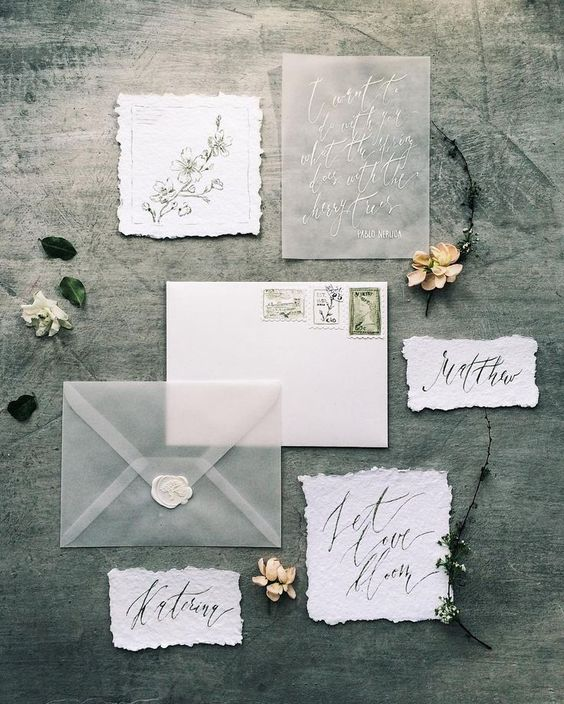 a matte acryl and calligraphy wedding invitation and a matching suite with raw edge paper cards