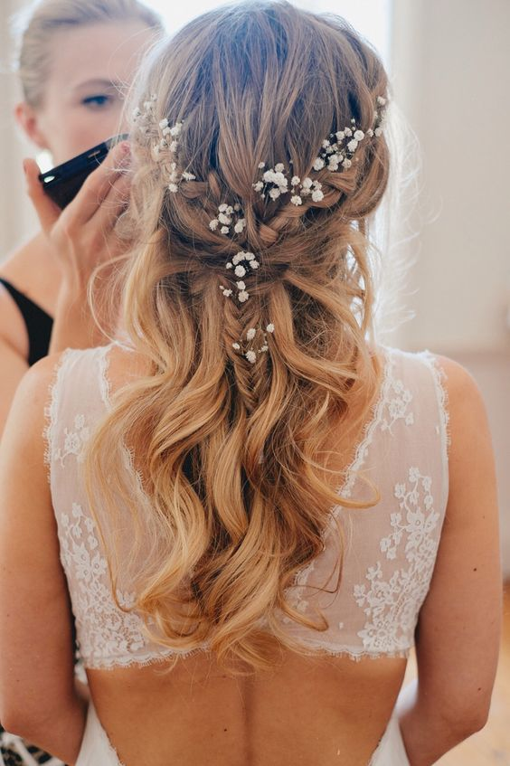 a twisted braided half updo with waves and baby's breath tucked in