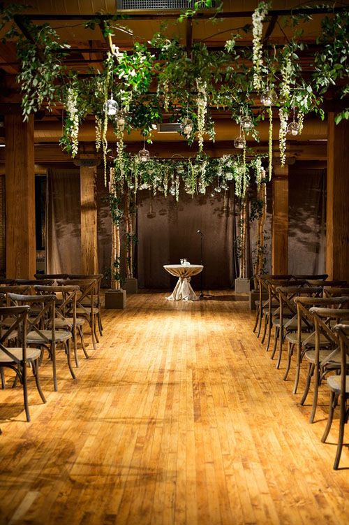 an industrial space with wooden pillars and hanging greenery and candle holders