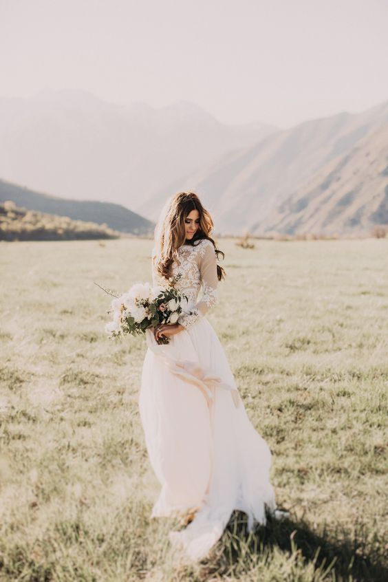 a chic wedding dress with an illusion bodice, long sleeves and a flowy skirt for eloping to the mountains