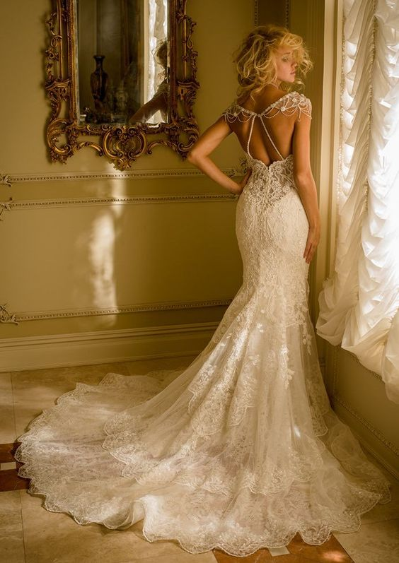 a gorgeous lace wedding dress with a train and shoulder jewelry