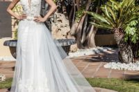 11 a textural lace embellished bodice with a covered plunging neckline and a tulle overskirt with a train