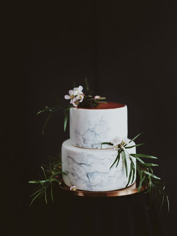 blue marbleized wedding cake with a copper top and foliage for decor