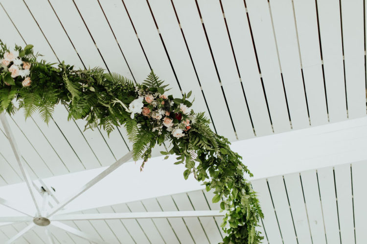 Floral chandeliers were made of large wheels, greenery and blush blooms