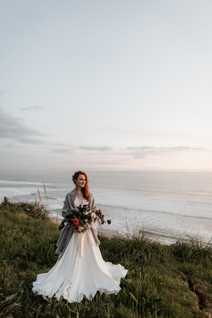 The bride covered up with a comfy grey shawl on the shore
