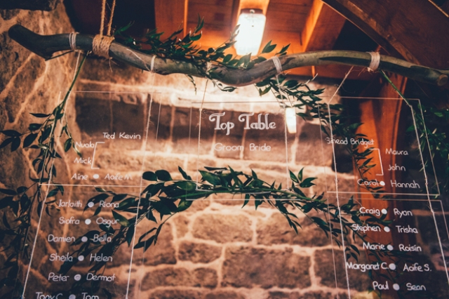 The table plan was made of lucite, hung on a branch and decorated with fresh greenery