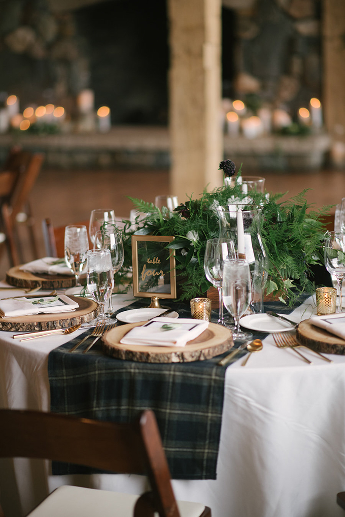 Wood slice chargers with greenery and some gilded touches made the tablescapes cozy