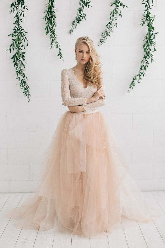a champagne-colored wedding dress with a lace bodice, a deep V-neckline, long sleeves and a layered skirt