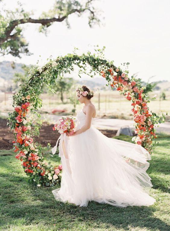 a greenery and red flower circle arch catches an eye with its shape and bold blooms