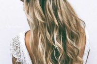 12 a wavy half updo with braids and blooms tucked into the hair