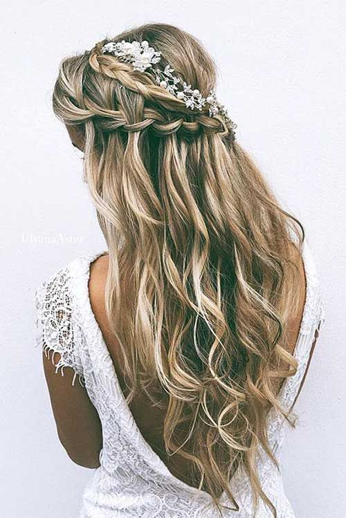 a wavy half updo with braids and blooms tucked into the hair