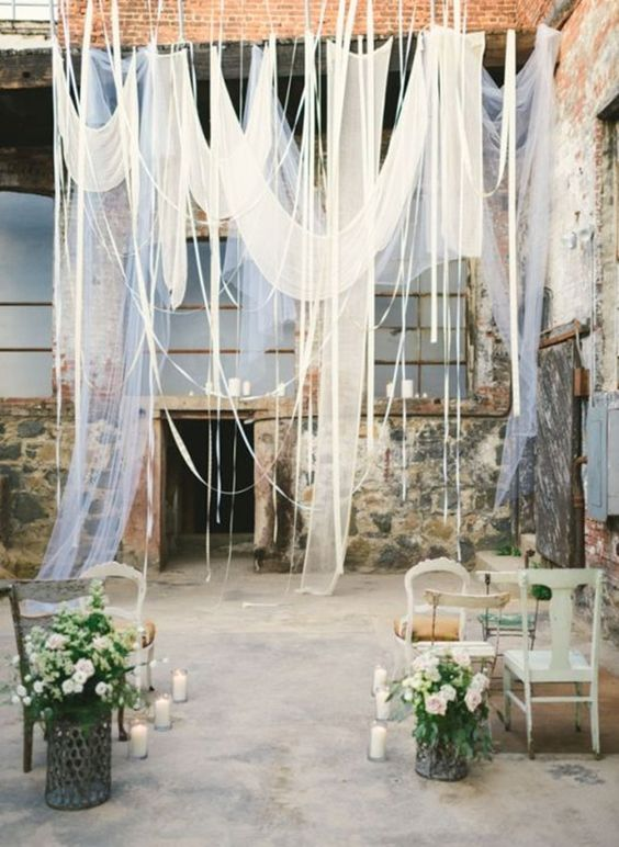 create a unique ceremony space with airy white fabric, ribbons and some greenery and flowers