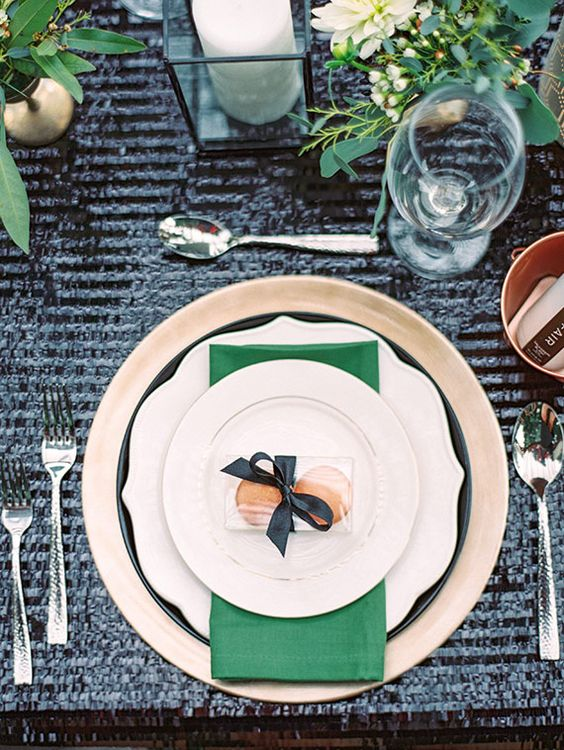 a chic gold and emerald table setting with a black sequin tablecloth as a chic backdrop