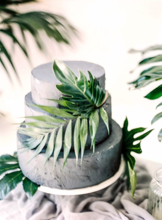 a concrete wedding cake with tropical leaves for a modern tropical wedding