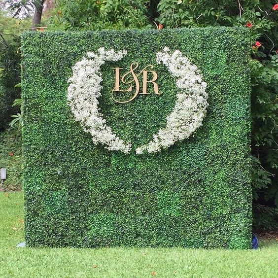 a greenery living wall with white bloom decor and gold monograms for an outdoor wedding