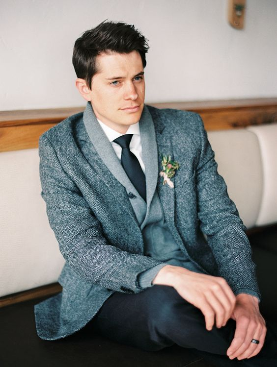 a grey cardigan, a grey tweed blazer over it and black pants and a tie for a comfy layered look
