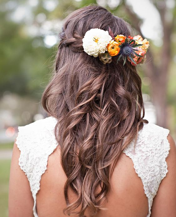a wavy braided half updo with fresh blooms that fit the wedding bouquet