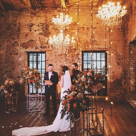 the cermeony space decorated with glam chandeleirs, lights and lush florals on stands