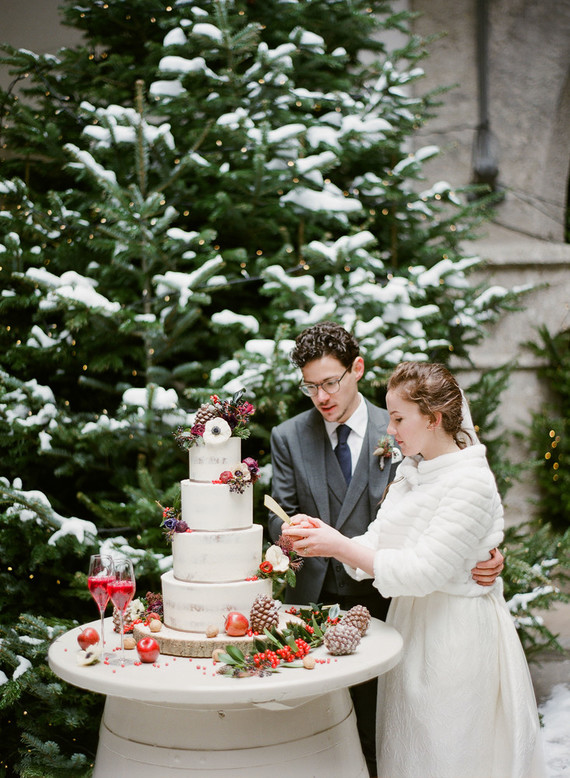 The wedding cake was done with flowers, fruits, greenery, berries, pinecones and apples