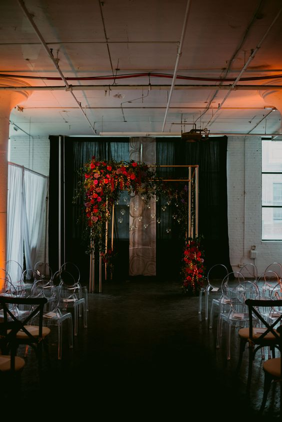 a copper wedding arch with lush red blooms and candles hanging for an industrial wedding