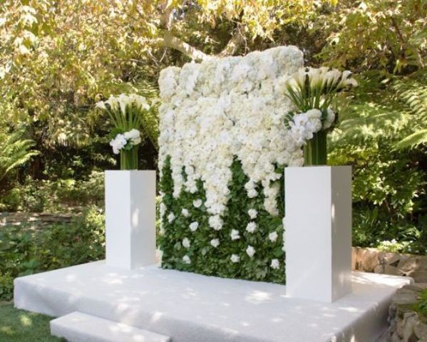 a large greenery and white floral wall and white orchids on both sides of the wall