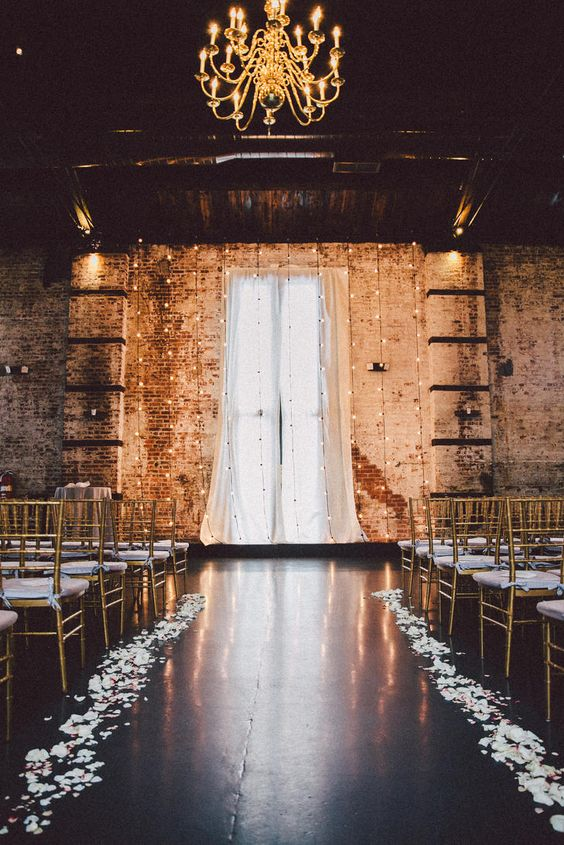 the ceremony space with shabby brick walls, lights, petals and a gol chandelier