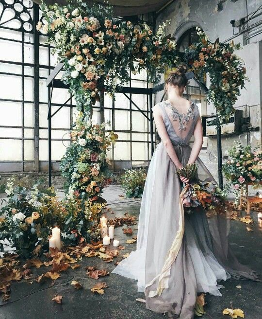 a fall-inspired floral arch in subtle pastel tones, with greenery and fall leaves placed inside